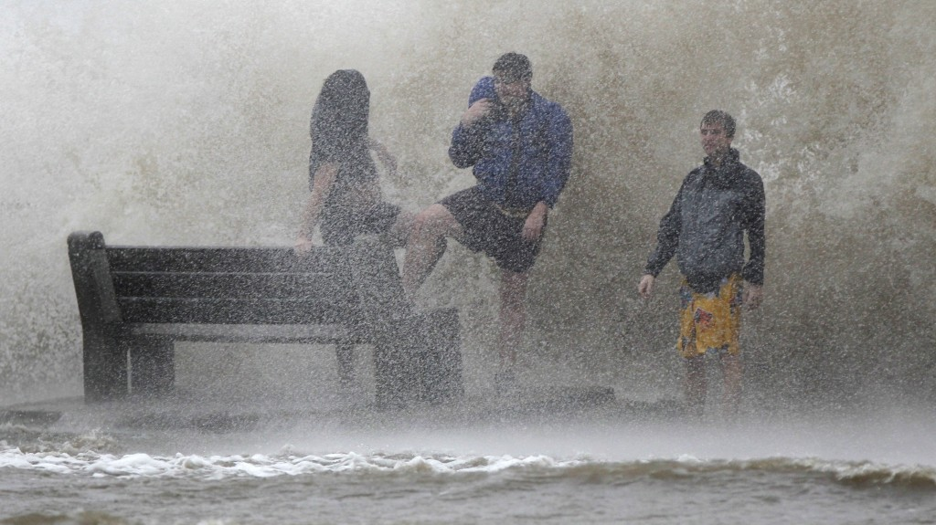 People walk in the storm surge from Hurricane Isaac along Lake Pontchartrain in New Orleans. Isaac was later downgraded to a tropical storm as it continued to grind its way through the Gulf Coast, dropping torrential rain and generating dangerous storm surges.